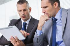 Focused businessmen analyzing documents on their tablet Stock Photos