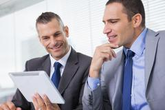 Stock Photo of Smiling businessmen working together on their tablet