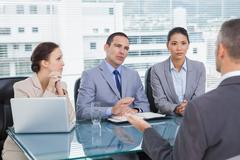 Serious business team interviewing experienced man - stock photo