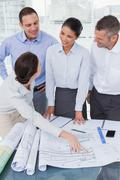 Happy architects interacting and analyzing plans together - stock photo