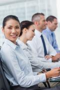 Cheerful employee attending presentation with her colleagues - stock photo