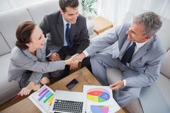 Business people shaking hands while working Stock Photos