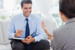 Smiling businessman talking to his colleague Stock Photos