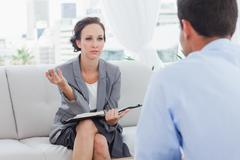 Serious businesswoman talking to her colleague - stock photo