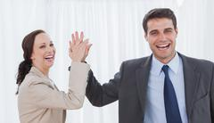 Cheerful workmates doing high five - stock photo