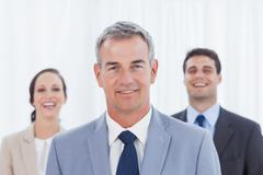 Experienced businessman posing with his work team - stock photo
