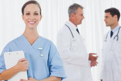 Stock Photo of Smiling surgeon posing while doctors talking on background