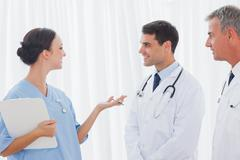 Doctors listening to their pretty workmate - stock photo