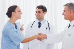 Surgeon thanking the doctor for helping her - stock photo