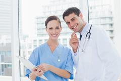 Cheerful surgeon and doctor posing while working together - stock photo