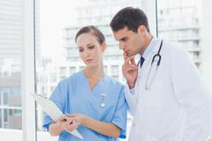 Focused surgeon and doctor working together - stock photo