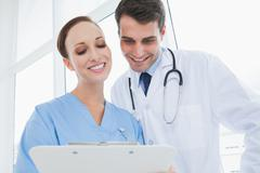 Cheerful doctor and surgeon viewing documents together - stock photo
