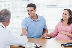Smiling man shaking hands with his doctor while holding his expecting wifes hand Stock Photos