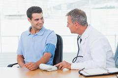 Stock Photo of Doctor taking blood pressure of smiling patient