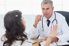 Serious doctor listening to his patient talking - stock photo