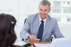 Smiling real estate agent completing contract with couple Stock Photos