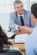 Smiling real estate agent shaking hands with his new buyer - stock photo