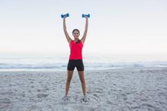 Stock Photo of Cheerful sporty woman holding dumbbells