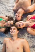 Stock Photo of Overhead of smiling friends lying together in a circle