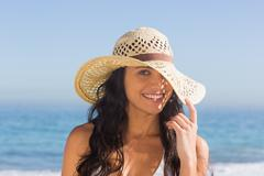 Stock Photo of Attractive dark haired woman with straw hat posing