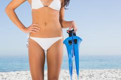 Perfect female body in white bikini holding fins Stock Photos