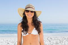 Smiling attractive brunette with straw hat and sunglasses - stock photo