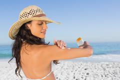 Stock Photo of Attractive brunette with straw hat putting on sun cream
