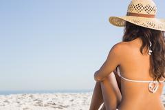 Stock Photo of Pensive attractive brunette in white bikini sitting