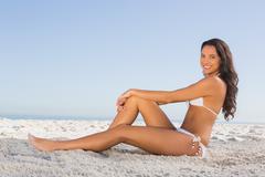 Cheerful attractive brunette in white bikini posing while sitting - stock photo