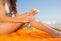 Close up of attractive young woman applying sun cream Stock Photos