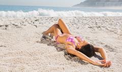 Sexy brown haired woman in pink bikini lying - stock photo