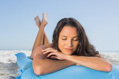 Stock Photo of Pensive attractive brunette relaxing on her lilo