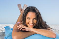Smiling attractive brunette relaxing on her lilo - stock photo