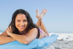 Stock Photo of Smiling attractive brunette lying on her lilo