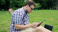 Young male student with tablet computer in the park HD - stock footage