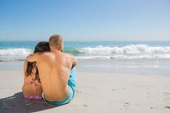 Sexy couple sitting while looking at the sea - stock photo