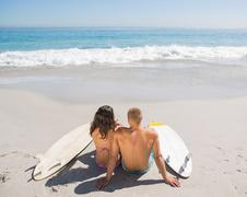 Young couple with their surfboards looking at the sea - stock photo