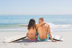 Pretty young couple sitting with their surfboards - stock photo