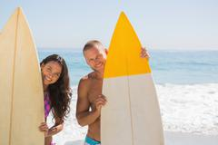 Cute young couple holding their surfboards - stock photo