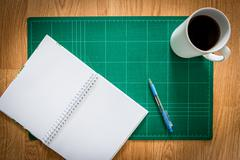 Cutting mats , notebook , pen , cup of coffee on the wood background Stock Photos