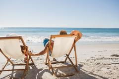 Cute couple lying on their deck chairs - stock photo