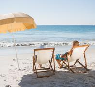Cute couple sunbathing on their deck chairs - stock photo
