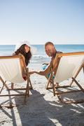 Cute couple smiling at camera while lying on their deck chairs Stock Photos