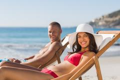 Young couple on their deck chairs smiling at camera - stock photo