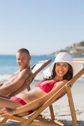 Couple on their deck chairs smiling at camera - stock photo