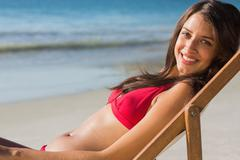 Smiling pretty woman relaxing on her deck chair - stock photo