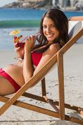 Cheerful pretty woman drinking cocktail while relaxing on her deck chair - stock photo