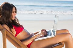 Attractive woman using her laptop while relaxing on her deck chair - stock photo