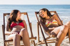 Cheerful beautiful friends relaxing on their deck chairs - stock photo