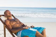 Handsome man having a nap while sunbathing on his deck chair - stock photo